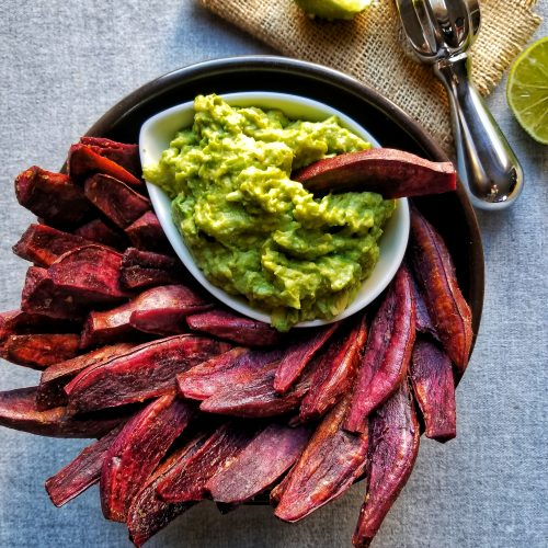 purple sweet potato wedges in a black bowl with guacamole