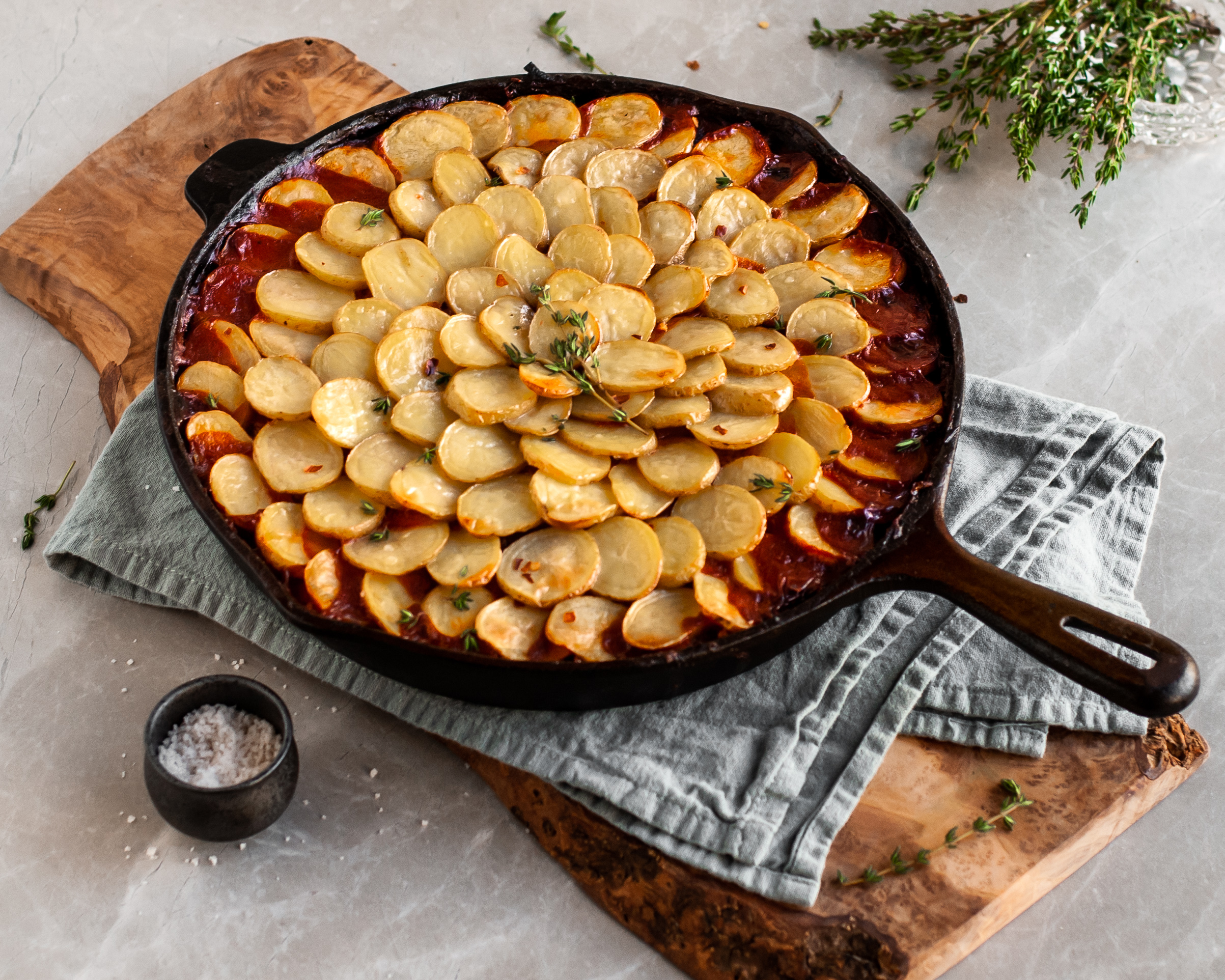 Vegan Savory Skillet Stew with Baby Potato Topping cooling on tea towel over wood slab