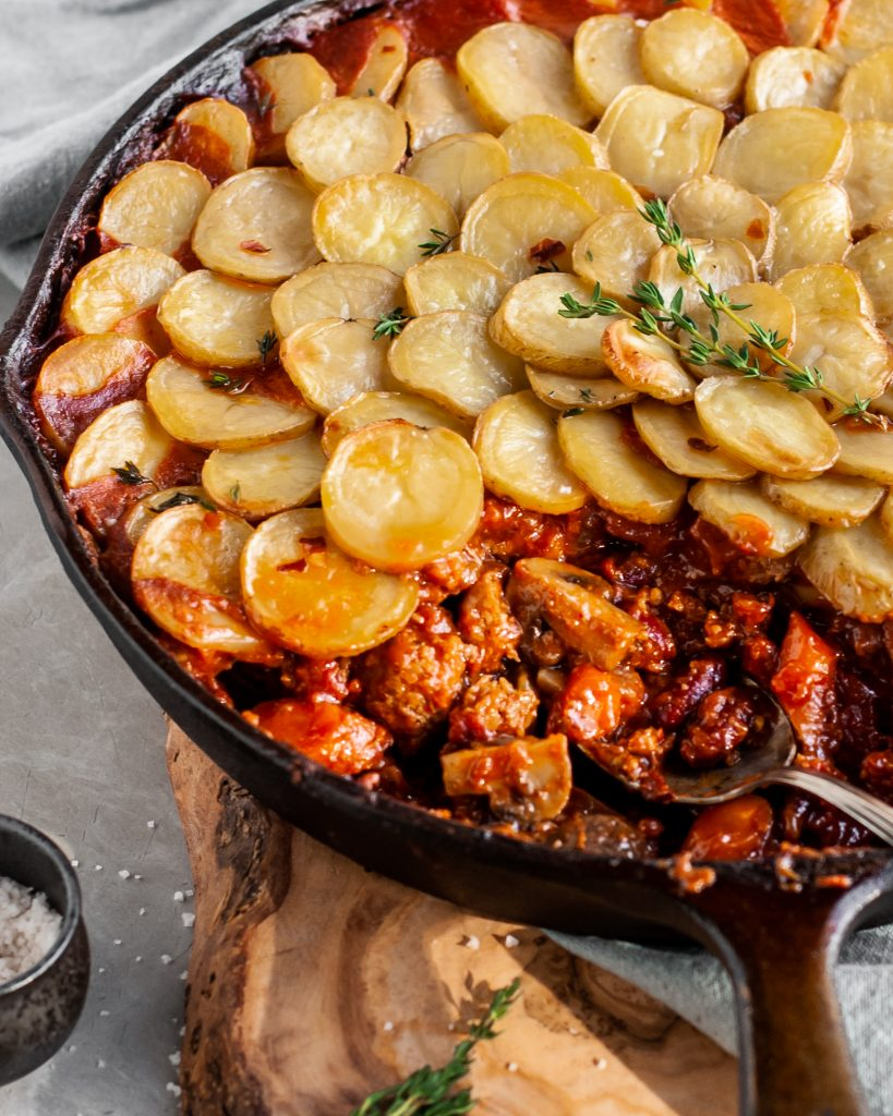 Vegan Savory Skillet Stew with Baby Potato Topping being served from skillet