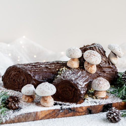 """Vegan Chocolate Yule Log with Meringue Mushrooms served on a plank covered in icing sugar """"snow"""""""