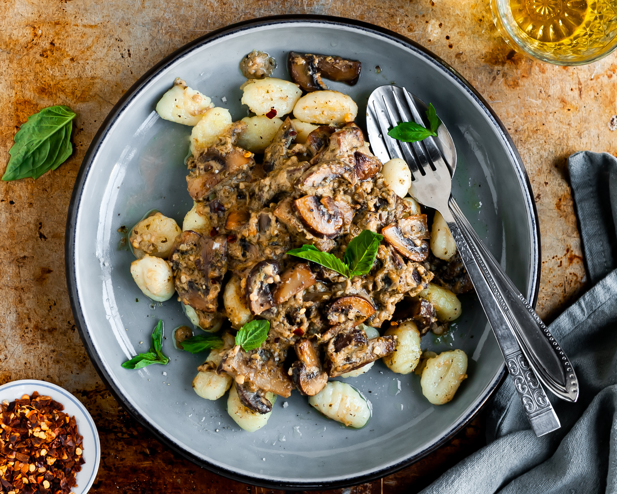Plate filled with Pan-Fried Gnocchi and Seared Mushrooms in a Cashew Butter Pesto Sauce served with chilli flakes, fresh basil