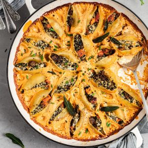 Round white skillet filled with pasta shells stuffed with butternut squash, vegan ricotta