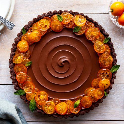 Vegan Chocolate Orange Tart with Candied Kumquats sits beside serving plates and fresh kumquats