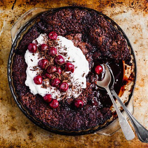 Vegan Saucy Cherry Chocolate Fudge Cake served with coconut whipped cream and morello cherries