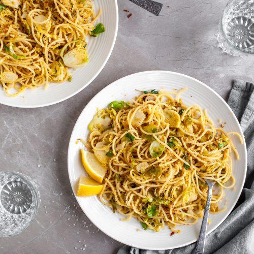 15 Minute Garlicky Breadcrumb Pasta with Shredded Brussels Sprouts served on white plates with chili flakes
