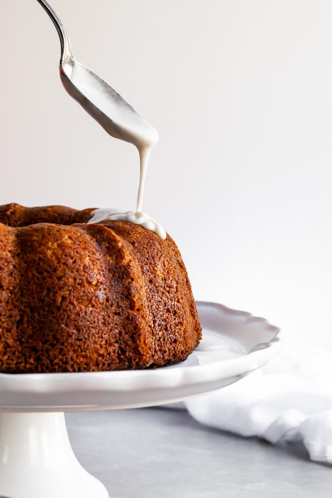 Vegan Hummingbird Cake being drizzled with vanilla glaze