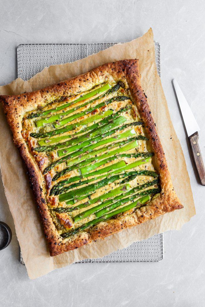 Vegan Asparagus and Pesto Cashew Cheese Tart with Lemon Arugula on cooling rack before arugula salad is added