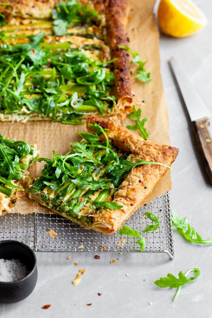 Vegan Asparagus and Pesto Cashew Cheese Tart with Lemon Arugula on cooling rack and a close up of one cut slice