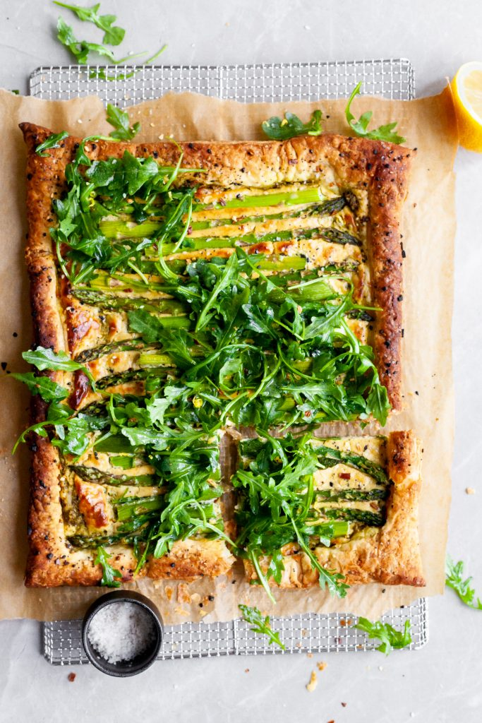 Vegan Asparagus and Pesto Cashew Cheese Tart with Lemon Arugula on cooling rack with one slice cut