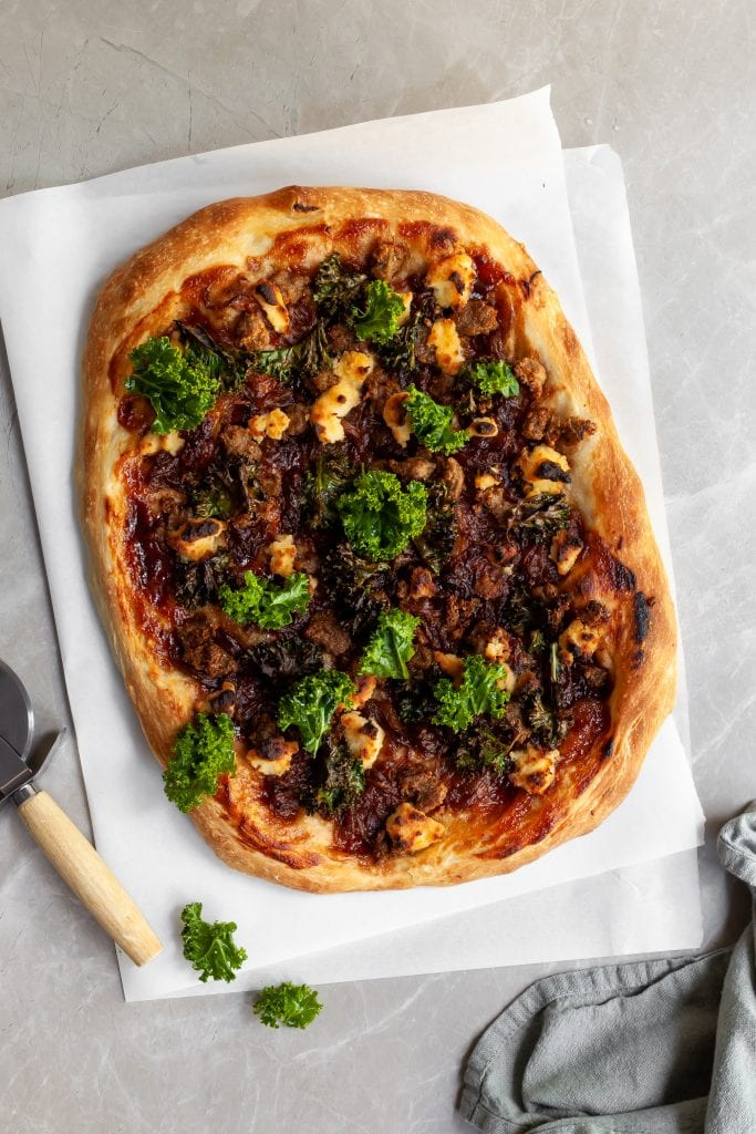 Flaylay of the pizza fresh from the oven and some fresh kale sprinkled on top