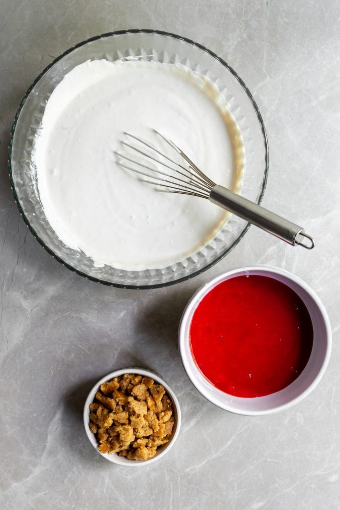 Prepared cashew base for the the ice cream in a large bowl, strawberry rhubarb sauce in a medium bowl and the crumbles in a small bowl