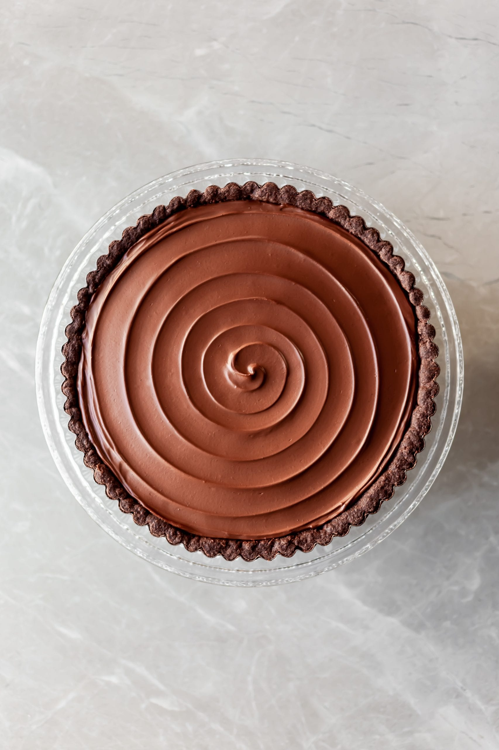 Vegan Chocolate Orange Tart with a swirl through the ganache on top prior to the candied kumquats being placed