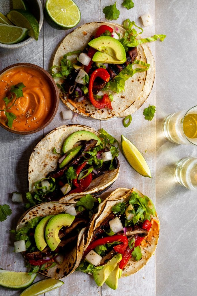 Looking down on 4 Korean Portobello Tacos served with lime wedges and Gochujang Crema