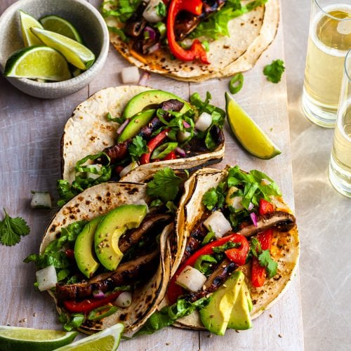 Vegan Korean Tacos served on a white wood board with a side of limes and a glass of beer