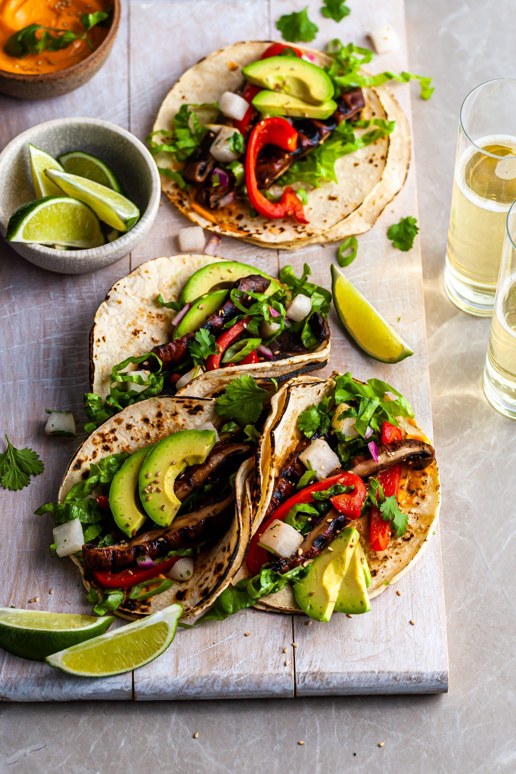 4 Korean Mushroom Tacos on a white serving board served with lime wedges, Gochujang crema and beer