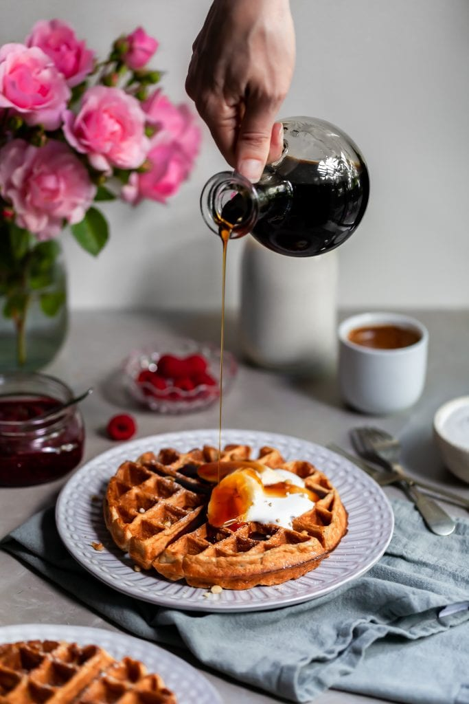 Vegan Banana Waffles served with vegan cream, fresh bananas and a bottle of maple syrup being poured over them.
