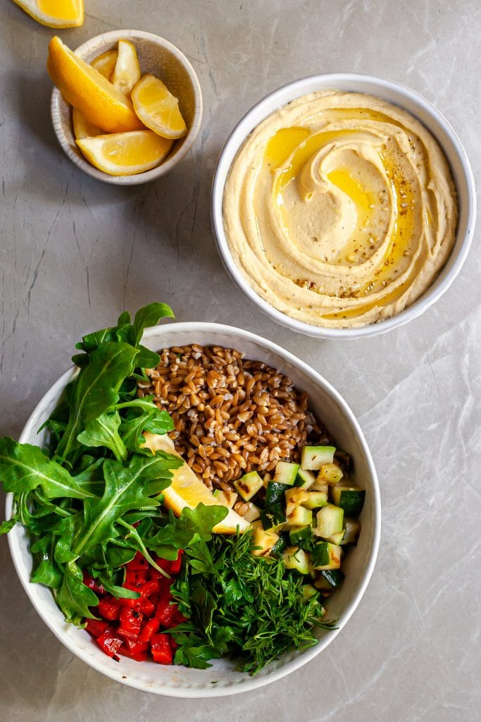 Ingredients for the farro salad in a large bowl before tossing, hummus in  a second bowl and lemon wedges in a third bowl.