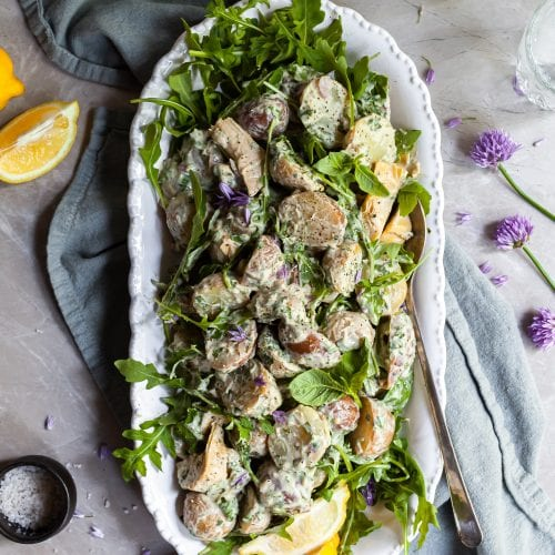 Potato salad on a white platter, garnished with fresh lemons and chive blossoms