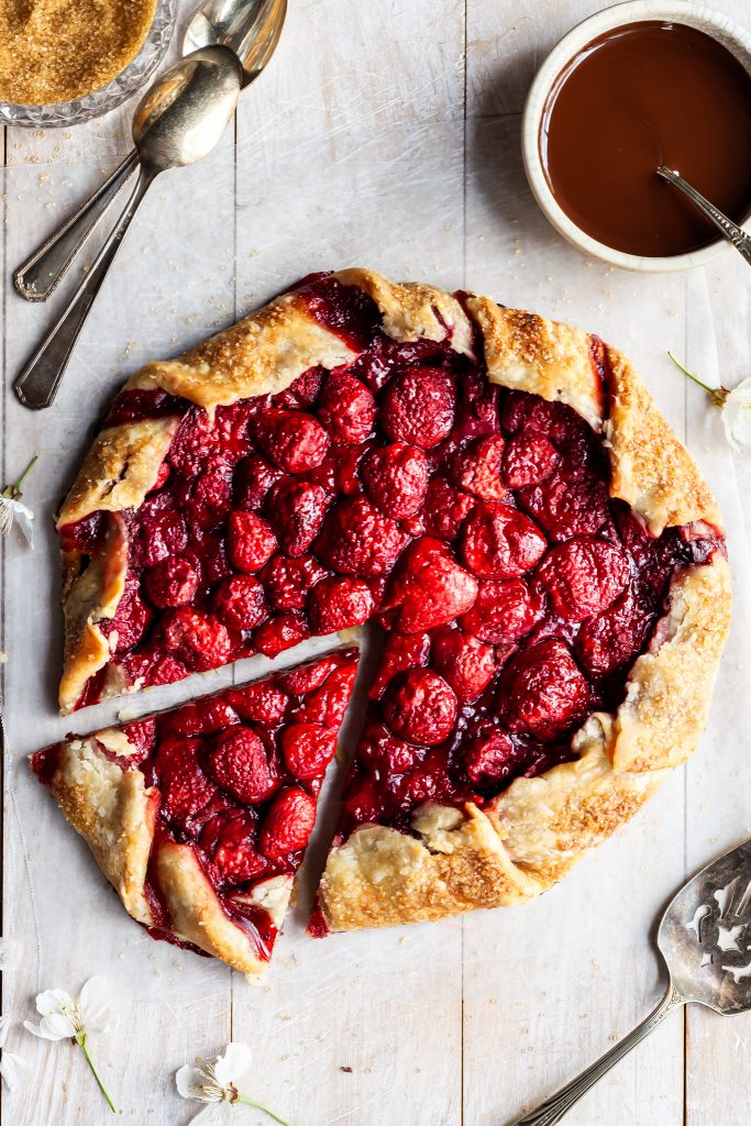 Fresh baked strawberry galette with one slice cut beside a white bowl of chocolate hazelnut sauce
