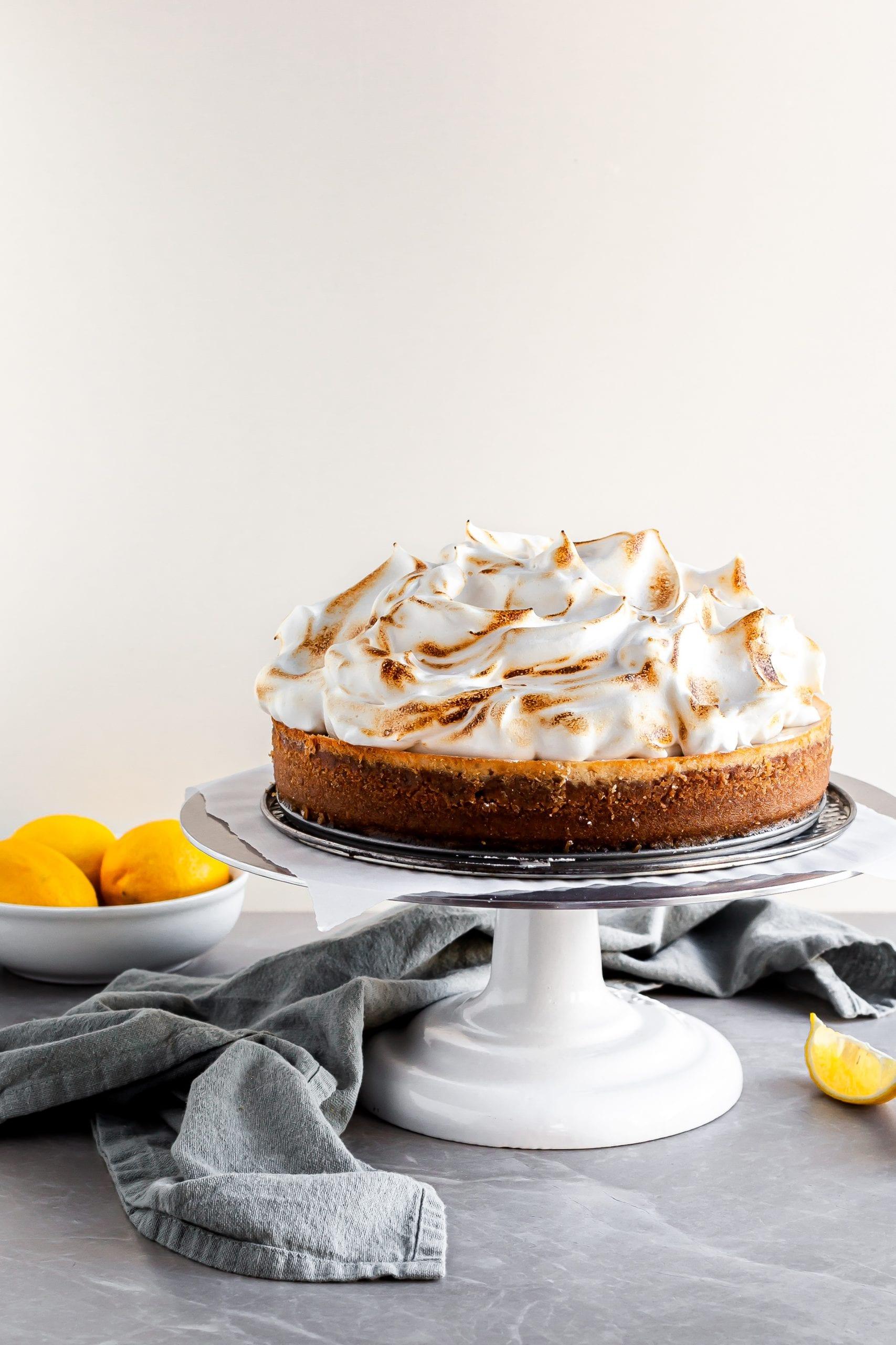 Vegan Lemon Meringue Cheesecake on a white cake stand beside a bowl of lemons