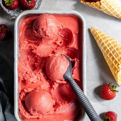 Flatlay of strawberry rhubarb sorbet scoops in a rectangular pan beside a dish of fresh strabwerries and some ice cream cones