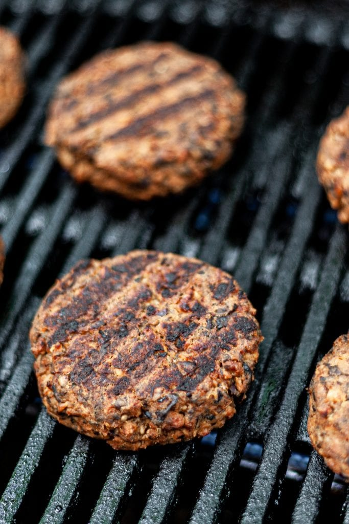 Veggie patties flipped on grill showing char marks
