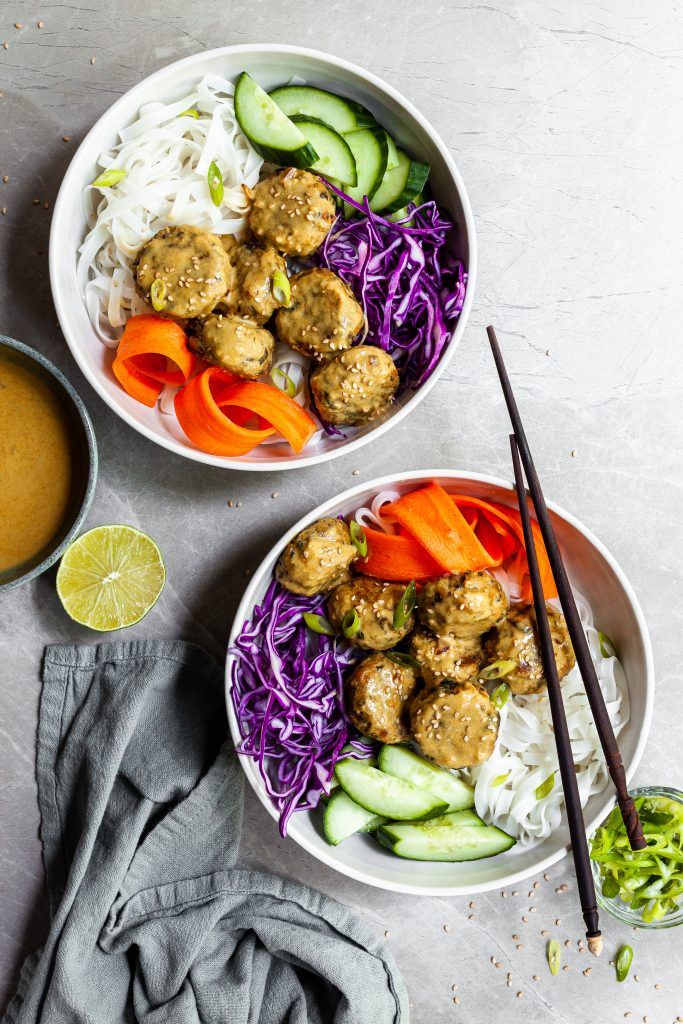 Two white Thai noodles bowls with chickpea meatballs and fresh vibrant veggies, served with a side bowl of yellow curry sauce