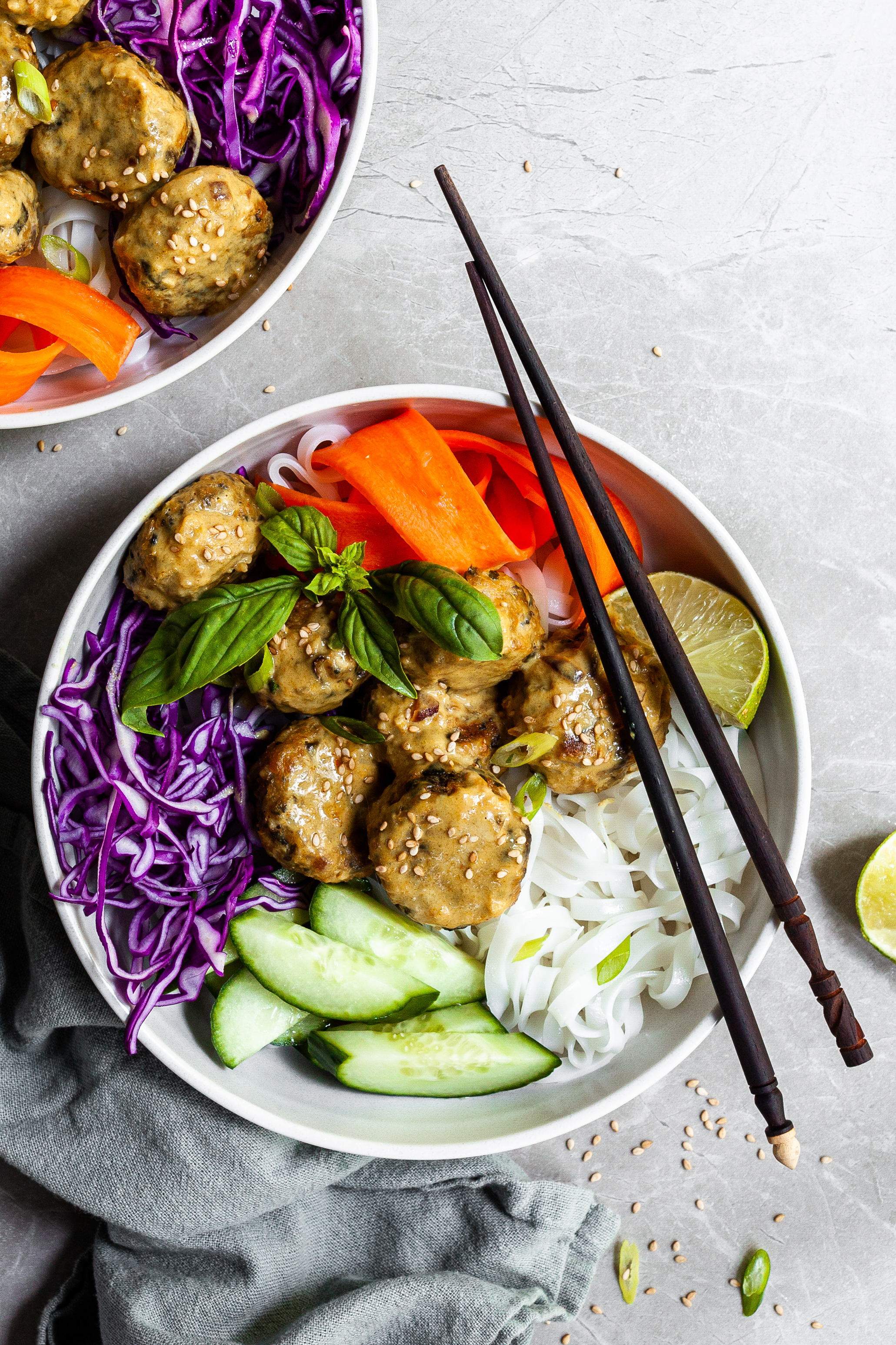 White bowl and chopsticks with rice noodles, chcikpea balls covered in yellow curry sauce, and raw veggies