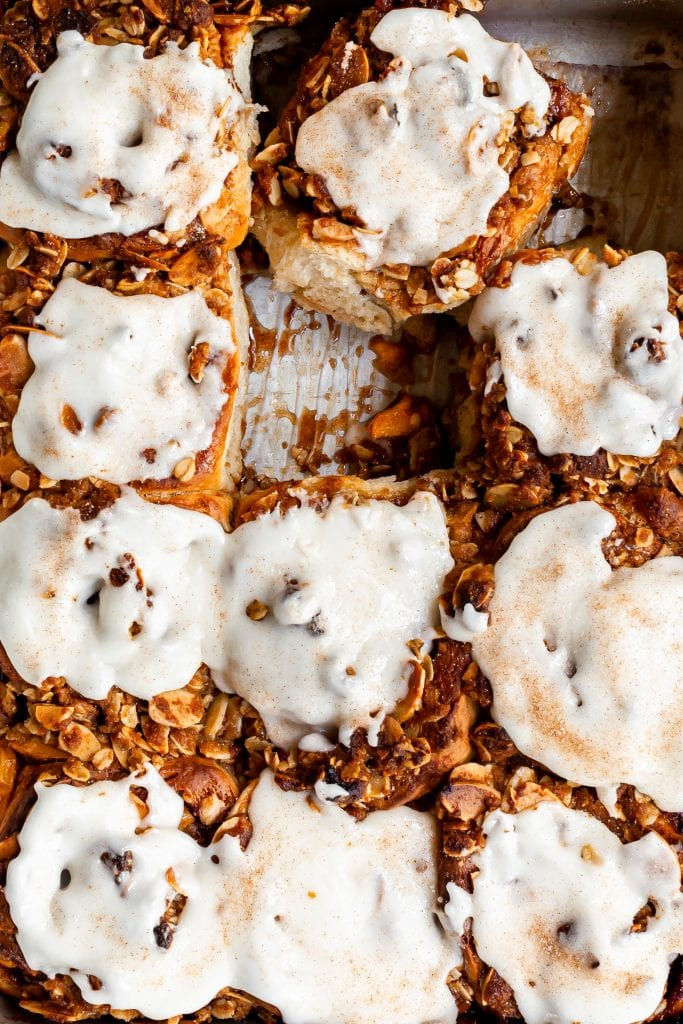 Close up of glazed cinnamon rolls in a pan