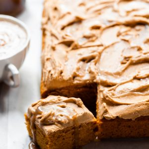 Sheet cake with swirled frosting served with a pumpkin spice latte and butterscotch sauce