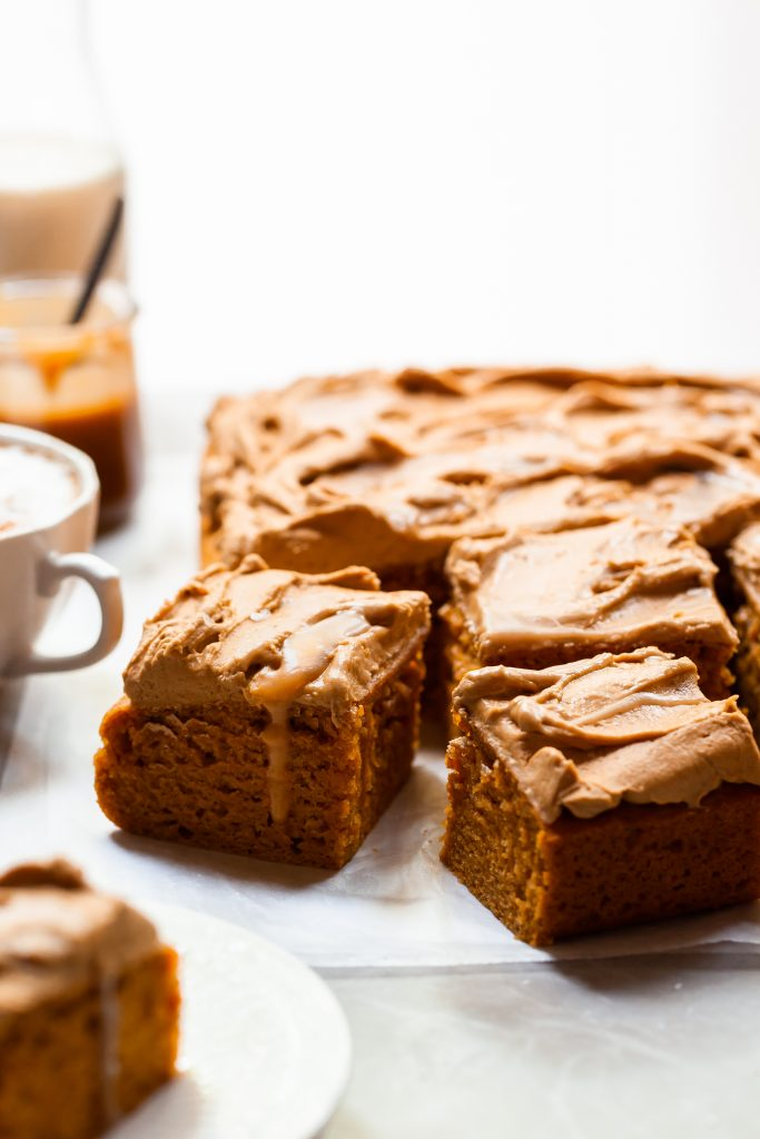 Sheet cake cut into square pieces, each covered in frosting and swirls of butterscotch, served with a pumpkin spice latte