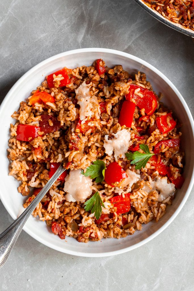 A white bowl filling with capsicum and rice bake