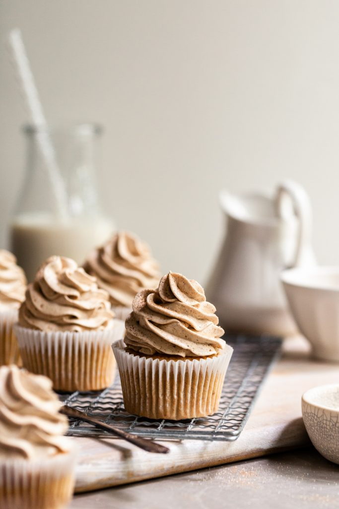 Frosted cupcakes on a cooling rack with a bottle of vegan milk in the background