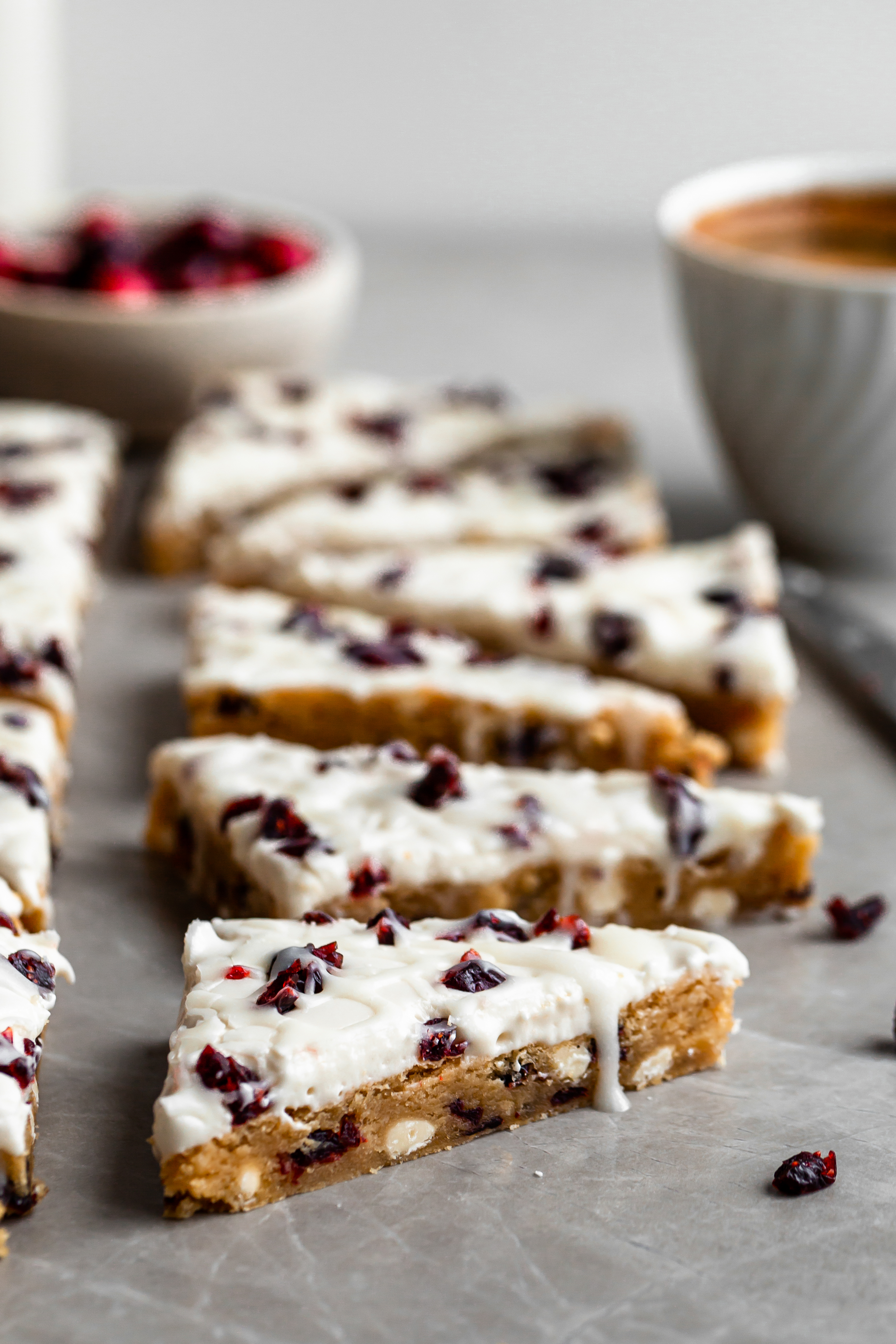 Vegan Cranberry Bliss Bars, cut into triangles and a cup of espresso in background