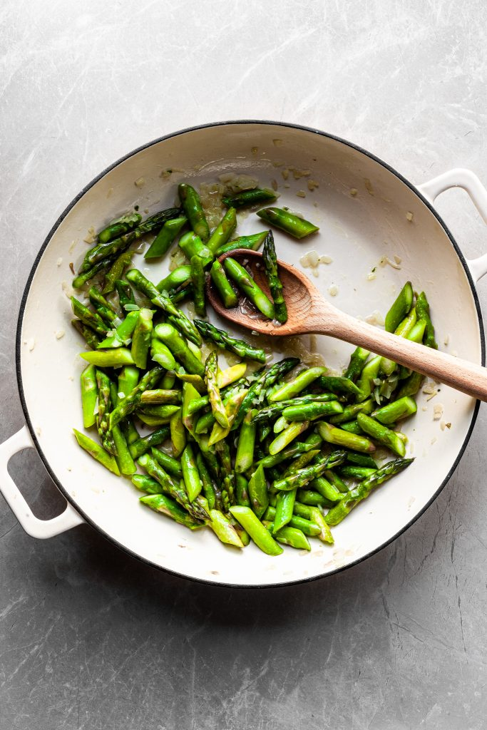 Flat lay of cooked asparagus in a white enamel skilllet