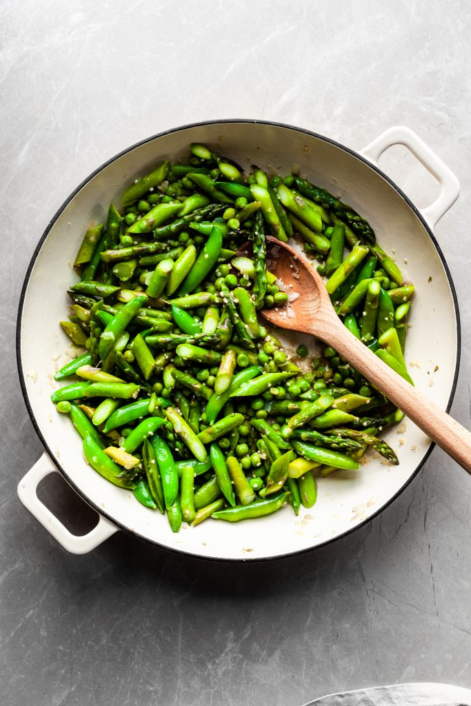 Flat lay of asparagus and peas in a white enamel skillet