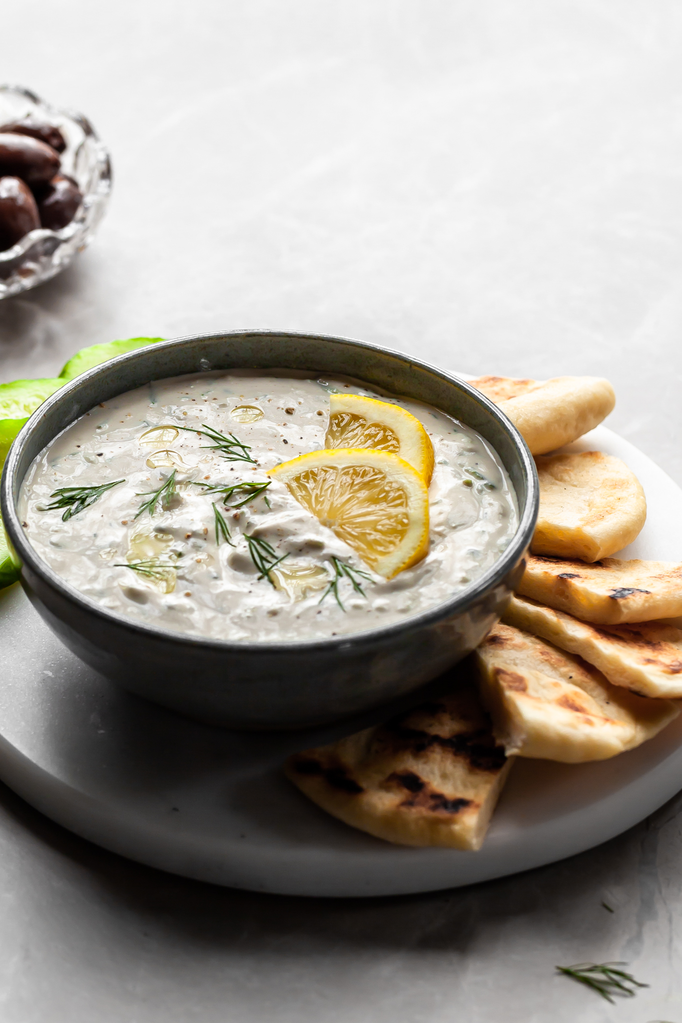 Grey bowl of tzatziki sauce garnished with lemon wedges, served with greek flatbread and slices of cucumber