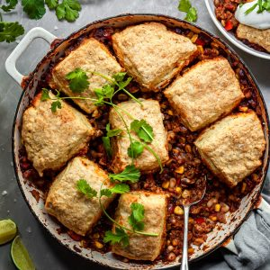 Chili pot pie in a white enamel skillet garnished with fresh cilantro leaves