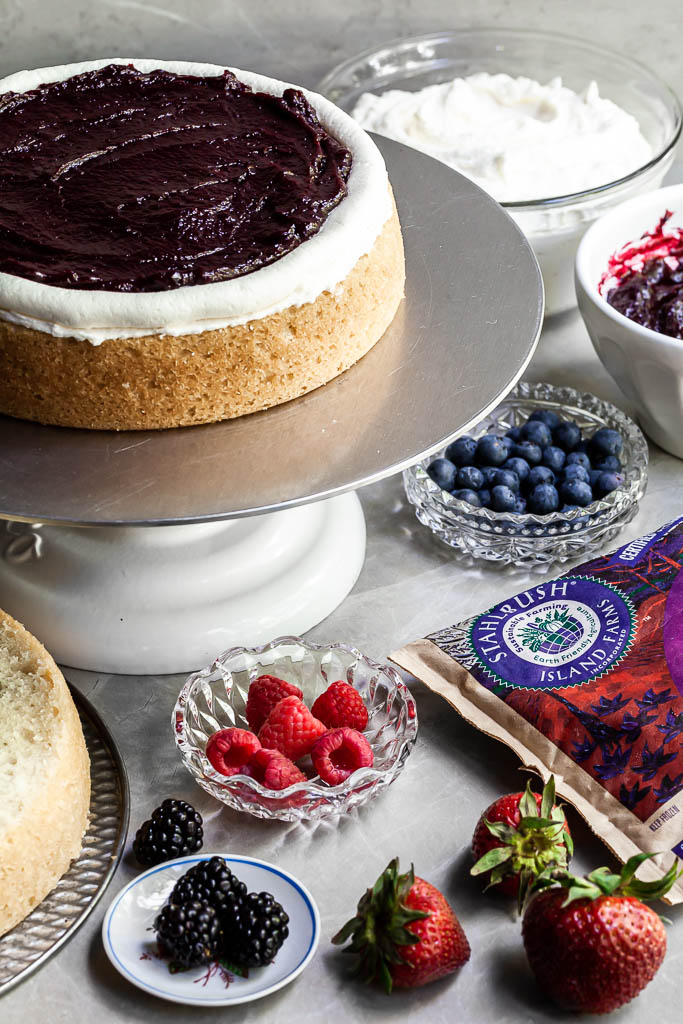The first layer of cake on a cake stand, covered in a layer of vanilla frosting and berry curd held in with a frosting dam. Bowls of fresh fruit sit beside the cake being assembled.
