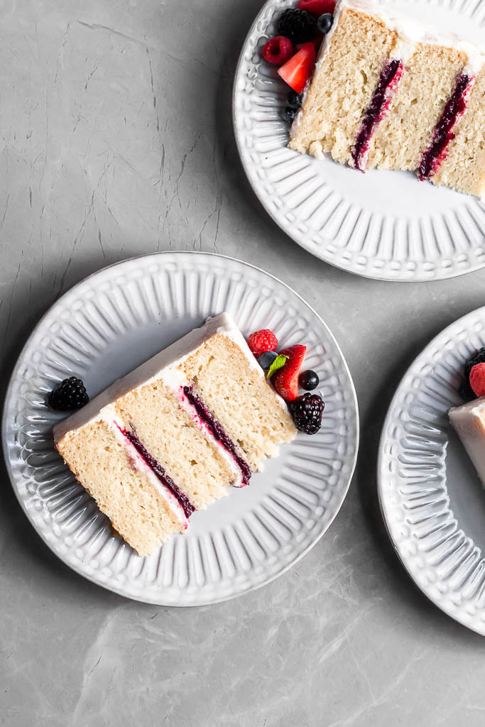 View looking down on 3 white plates on marble counter, each with a slice of berry vanilla cake.