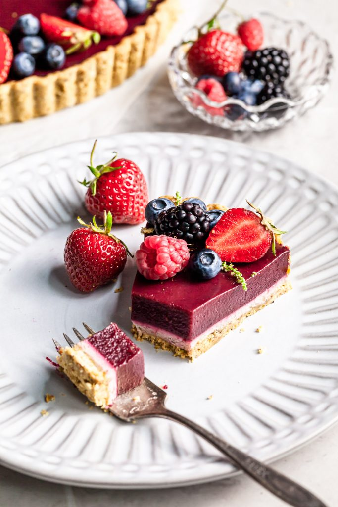 A bite of berry chocolate tart rests on a fork with the rest of the purple berry tart in the background on a white plate