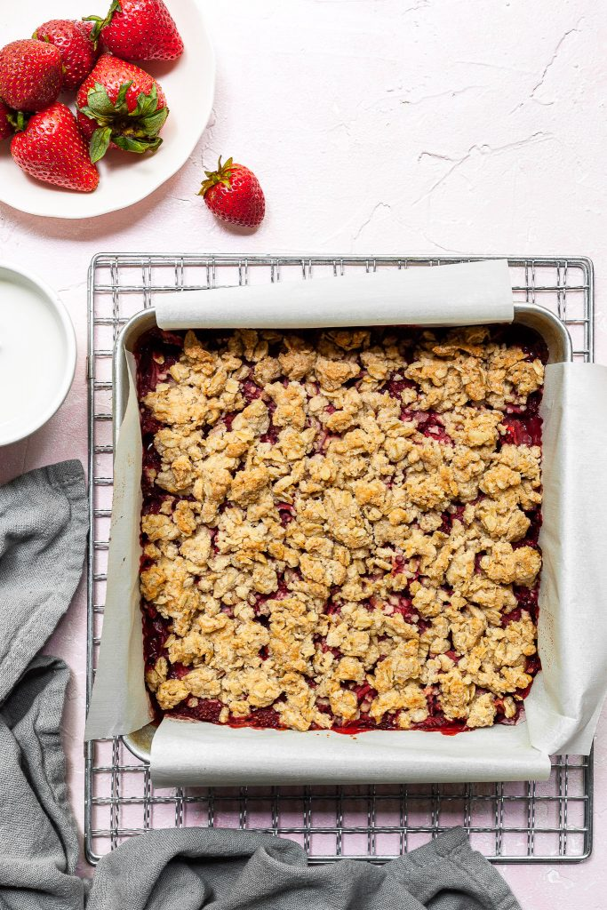 Square aluminium pan lined with parchment paper, filled with freshly baked strawberry crumb bars