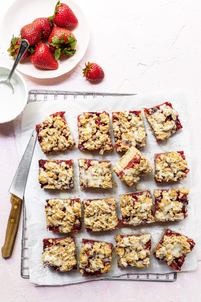 16 squares of strawberry crumb bars sitting on a wire cooling rack