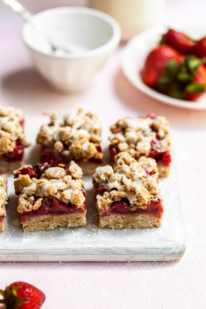 Close up of vegan strawberry crumb bars on a white cutting board, just drizzled with vanilla glaze