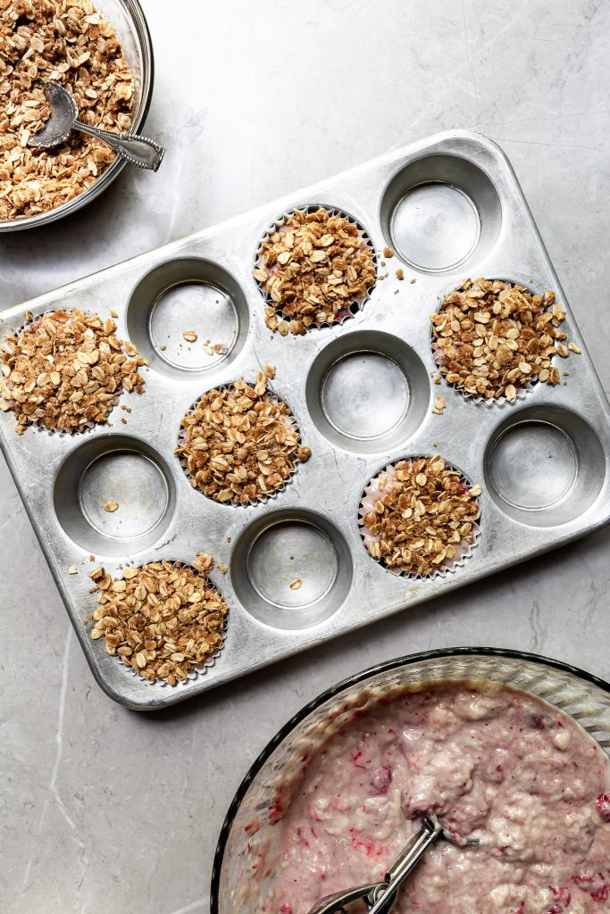 A muffin tin filled with batter and topped with oatmeal streusel, all ready for the oven