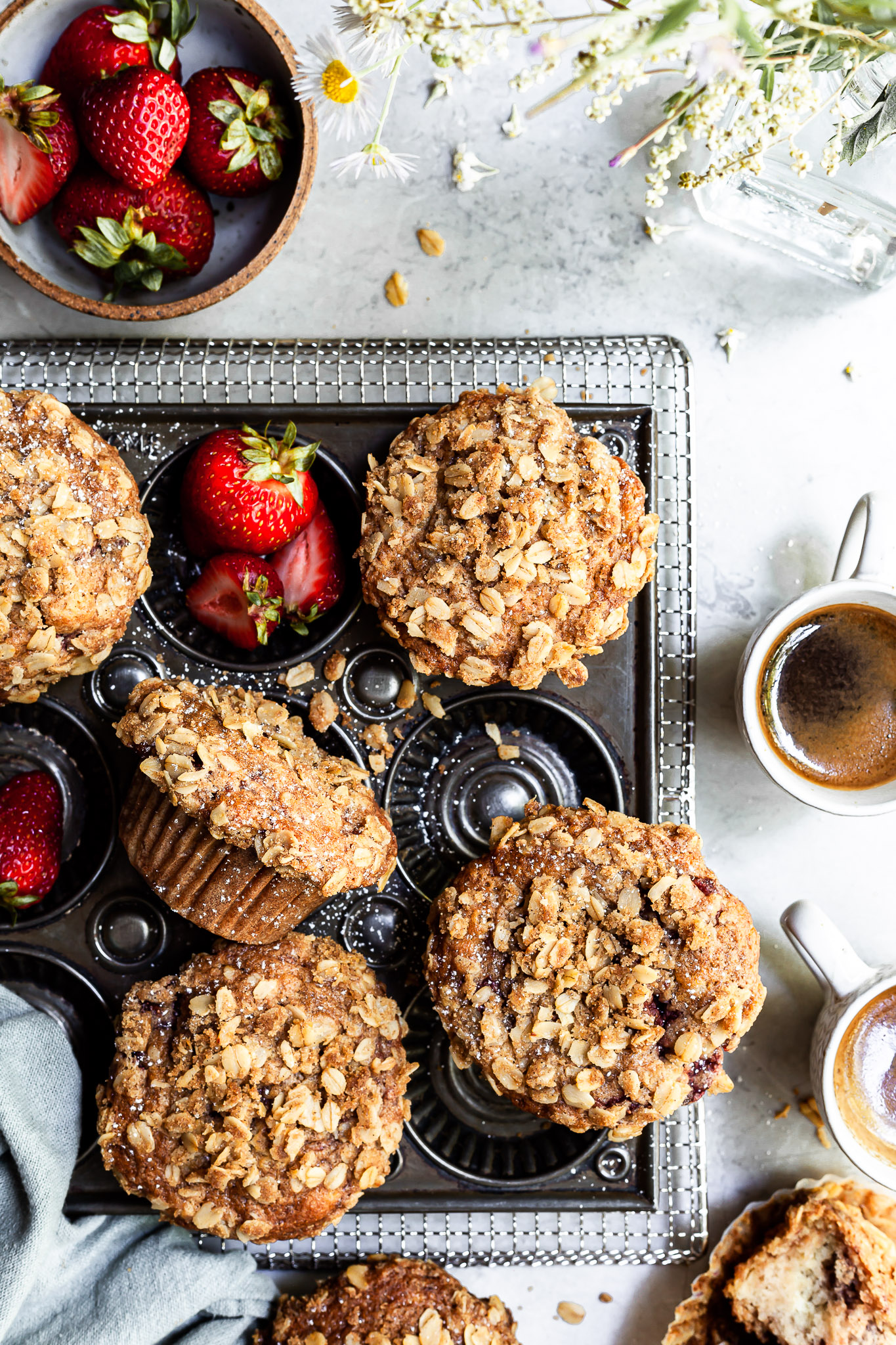 View looking down on a baking tray of muffins beside a bowl of strawberries, a vase of wildflowers and 2 some cups of espresso