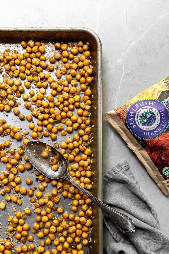 Baking tray filled with roasted chickpeas covered in sesame seeds