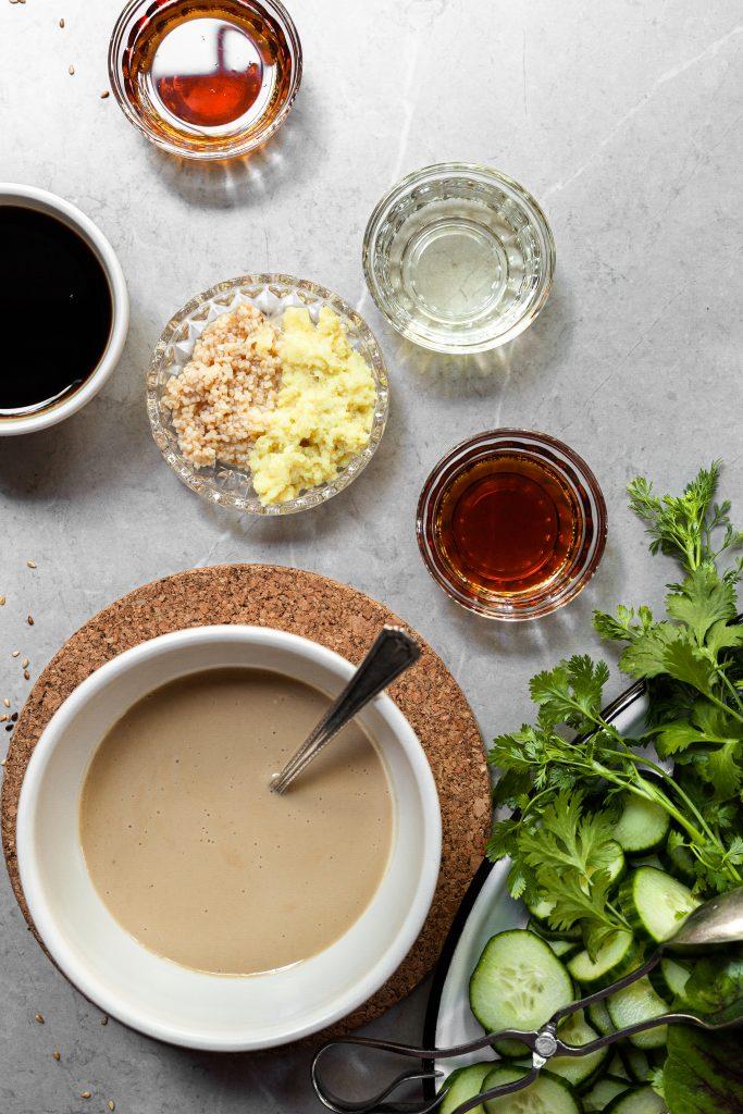 Ingredients measured out in bowls for sesame ginger sauce beside a platter of fresh vegetables