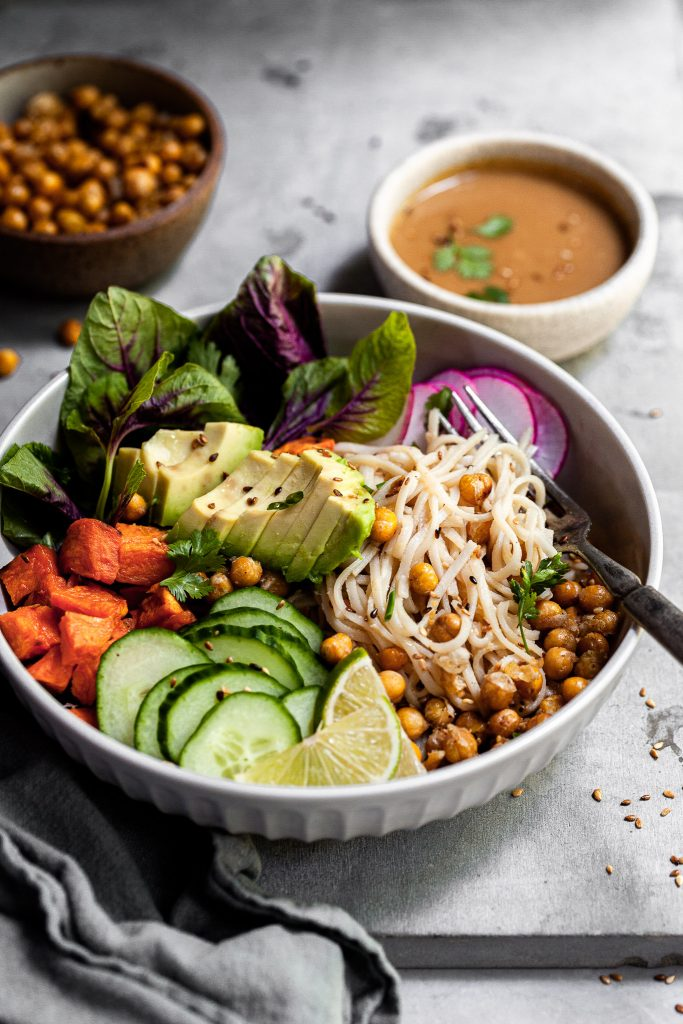 Side view into a bowl filled with rice noodles, roasted sweet potatoes, chickpeas, fresh veggies and sesame ginger sauce