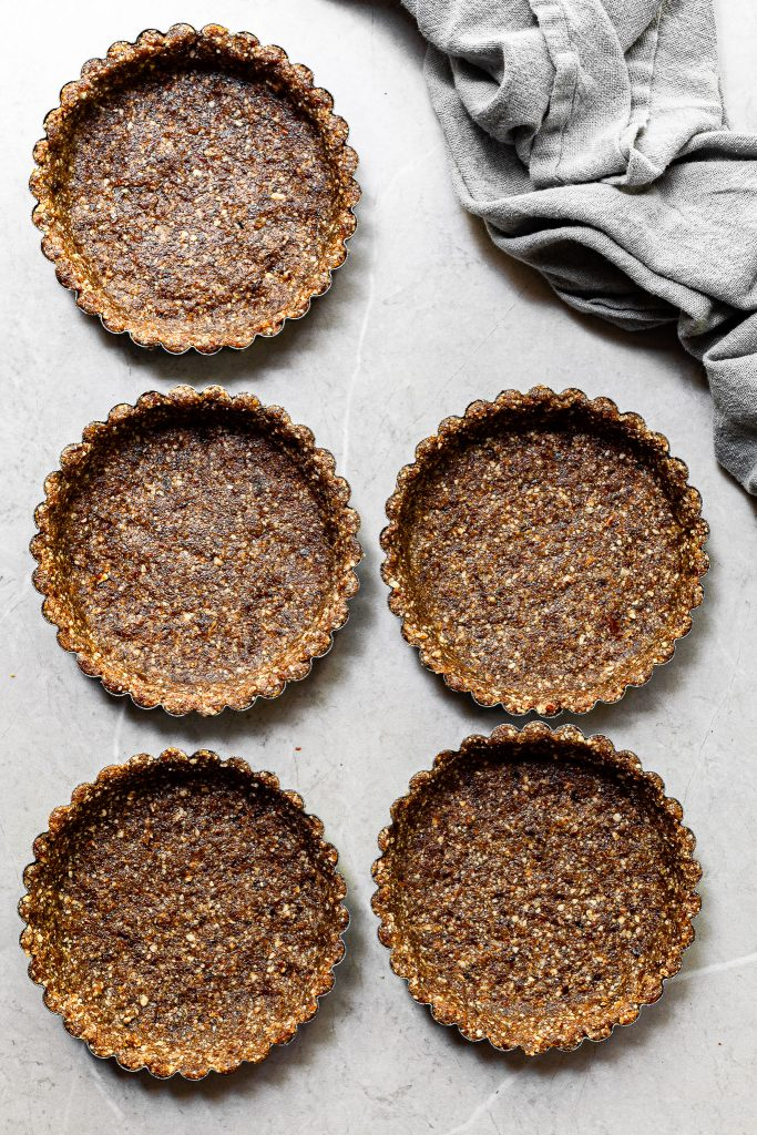 5 tart pans with the no-bake pecan date crust pressed into them